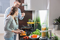 Happy man feeding food to woman cutting vegetables in kitchen