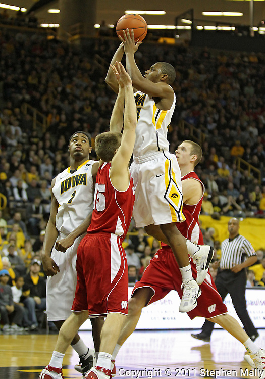 February 09 2011: Iowa Hawkeyes guard Bryce Cartwright (24) puts up a shot over Wisconsin Badgers guard Brett Valentyn (15) during the second half of an NCAA college basketball game at Carver-Hawkeye Arena in Iowa City, Iowa on February 9, 2011. Wisconsin defeated Iowa 62-59.