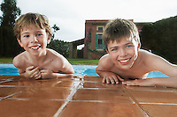 Portrait of two boys (6-11) leaning on edge of pool