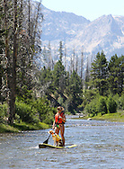 A stand-up paddleboarder navigates the Salmon River at the base of the Sawtooth Mountains a few miles north of Stanley, ID on Saturday July 13, 2013.