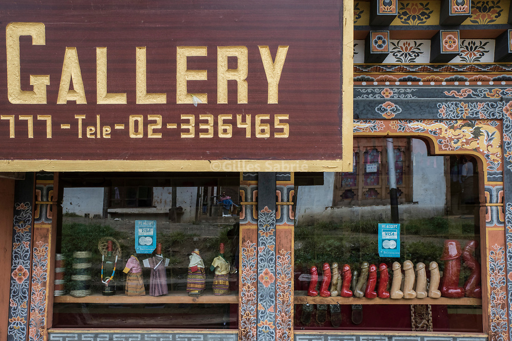 For a story by Steven Lee Myers, Bhutan<br /> Lobesa, Bhutan, August 2nd, 2017<br /> A souvenir store with wooden phalluses on display in its window. The tradition of painting phalluses on the walls of houses, in the village of Lobesa, has made the place a popular tourist spot. A legend says that Lobesa is where Lama Drukpa Kunley  popularly known as the &ldquo;Divine Madman&quot;  subdued a demon with his &ldquo;magic thunderbolt of wisdom&rdquo;. <br /> Gilles Sabri&eacute; pour The New York Times