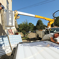 Josh Easley, of Tupelo and a employee at Duncan Signs, preps the wall at The Church of the Living God after removing an old sing, as Lee Duncan, owner of Duncan signs, gets the churches new sign ready to be lifted into place Wednesday morning in Tupelo. The church replaced their old sign with a new LED box sign.