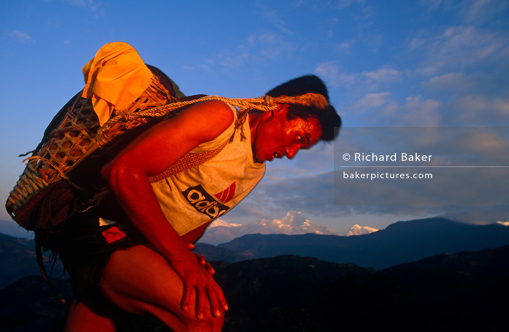 A young Nepali boy is undergoing a recruitment test for the Gurkha Regiment called the Doko race, part of a tough endurance series to find physically perfect specimens for British army infantry training. He has to carry 30kg of river stones in a traditional Himalayan doko (basket) for 3km up foothills within 37 minutes to pass.  60,000 boys aged between 17-22 (or 25 for those educated enough to become clerks or communications specialists) report to designated recruiting stations in the hills each November, most living from altitudes ranging from 4,000-12,000 feet. After initial selection, 7,000 are accepted for further tests from which 700 are sent down here to Pokhara in the shadow of the Himalayas. Only 160 of the best boys succeed in the journey to the UK. Nepal has been supplying youths for the British army since the Indian Mutiny of 1857.