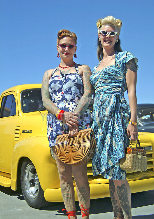 Two tattooed Rockabilly girls are posing infront of a Hotrod car, Viva Las Vegas Festival, Las Vegas, USA 2006.