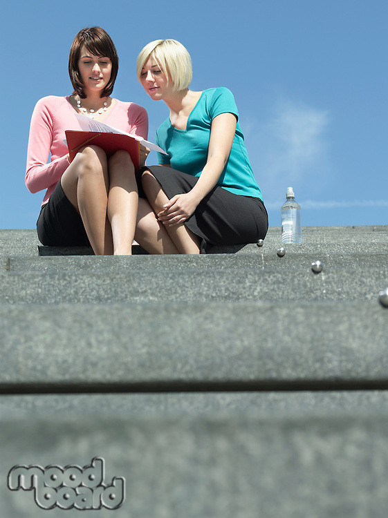 Two women sitting on stairs outdoors reading papers low angle view