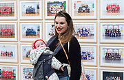 Steve McQueen Year 3 Exhibition<br /> at Tate Britain, London, Great Britain <br /> Press view <br /> 11th November 2019 <br /> <br /> Emmy visits the exhibition with baby Roma <br /> <br /> The Turner Prize-winning artist and Oscar-winning filmmaker has created one of the most ambitious visual portraits of citizenship ever undertaken in one of the world's largest cities. Using the medium of the traditional school class photograph, this installation brings together images of tens of thousands of Year 3 pupils from across London. It offers us a glimpse of the city's future - a hopeful portrait of a generation to come.<br />  <br /> <br /> Visitors interacting part of the installation<br /> <br /> A portrait of Turner Prize-winning artist and Oscar-winning filmmaker Steve McQueen with Tyssen Community School in the Duveens Galleries <br /> <br /> <br /> <br /> Photograph by Elliott Franks