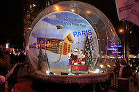 Santa Claus inside a giant snow globe on the Champs Elysees in Paris, France.