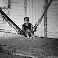 Boy swinging in a hammock on the front porch of his home in Bocas Del Toro, Panama