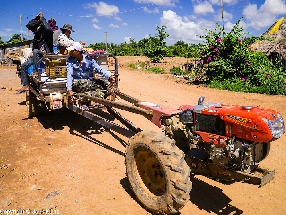 "29 JUNE 2013 - BATTAMBANG, CAMBODIA:   A loaded tractor leaves a rice mill in Reang Keseil near Battambang. The mill is next to the tracks that carry the ""bamboo trains."" The bamboo train, called a norry (nori) in Khmer is a 3m-long wood frame, covered lengthwise with slats made of ultra-light bamboo, that rests on two barbell-like bogies, the aft one connected by fan belts to a 6HP gasoline engine. The train runs on tracks originally laid by the French when Cambodia was a French colony. Years of war and neglect have made the tracks unsafe for regular trains.  Cambodians put 10 or 15 people on each one or up to three tonnes of rice and supplies. They cruise at about 15km/h. The Bamboo Train is very popular with tourists and now most of the trains around Battambang will only take tourists, who will pay a lot more than Cambodians can, to ride the train.       PHOTO BY JACK KURTZ"