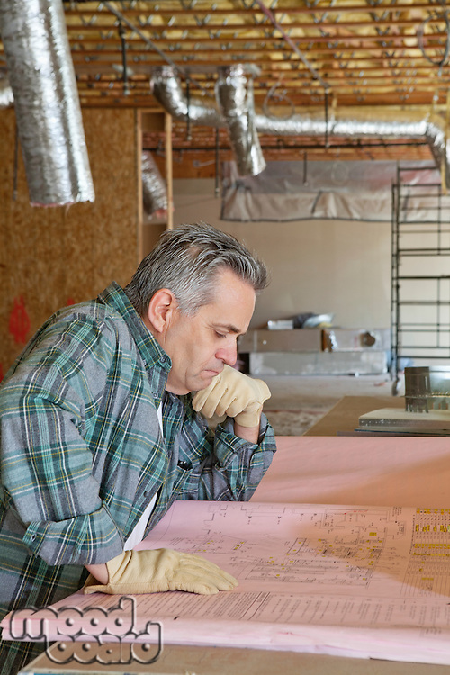 Side view of mature man looking at blueprint