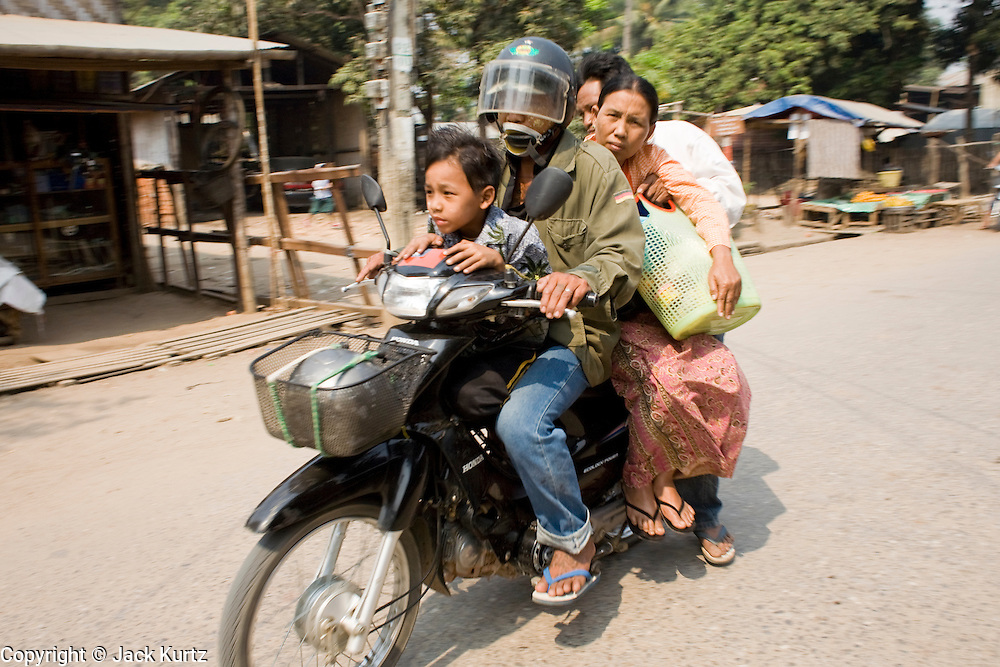 26 FEBRUARY 2008 -- MYAWADDY, MYANMAR: A family on a motor scooter in Myawaddy, Myanmar. Myawaddy is just across the Moei River from Mae Sot, Thailand and is one of Myanmar's leading land ports for goods going to and coming from Thailand. Most of the businesses in the town are geared towards trade, both legal and illegal, with Thailand. Human rights activists from Myanmar maintain that the Burmese government controls the drug smuggling trade between the two countries and that most illegal drugs made in Myanmar are shipped into Thailand from Myawaddy.   Photo by Jack Kurtz