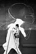 A street artist painting an artwork on a wall of DUMBO, brooklyn