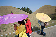 Tumuli Park. Tumuli are the hill tombs of Silla dynasty members. Girls with umbrellas.