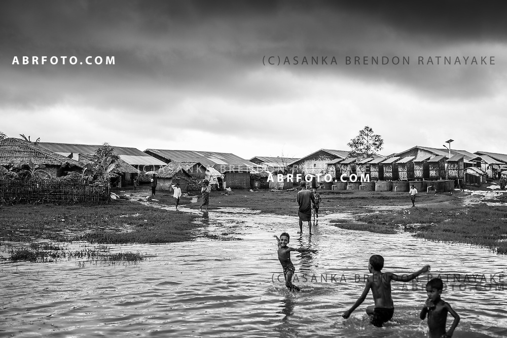 Young boys play in a flooded area inside the IDP camps in Sittwe