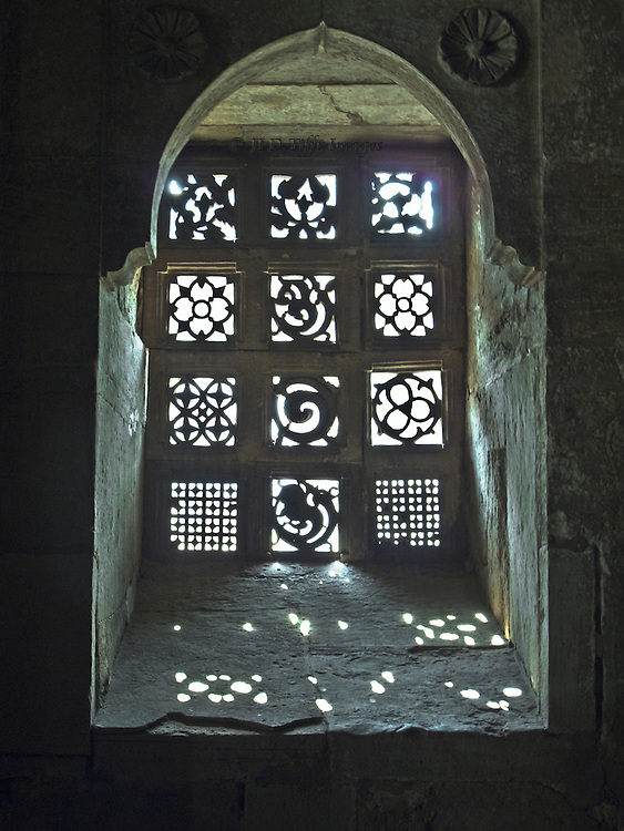 Pierced stone window grille in the mosque of Ahmad Shah 1, Ahmedabad, seen from the interior, with sunlight projected onto the sill and embrasure.