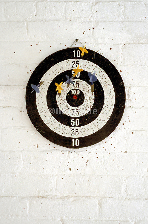 darts on dart board on white painted brick wall