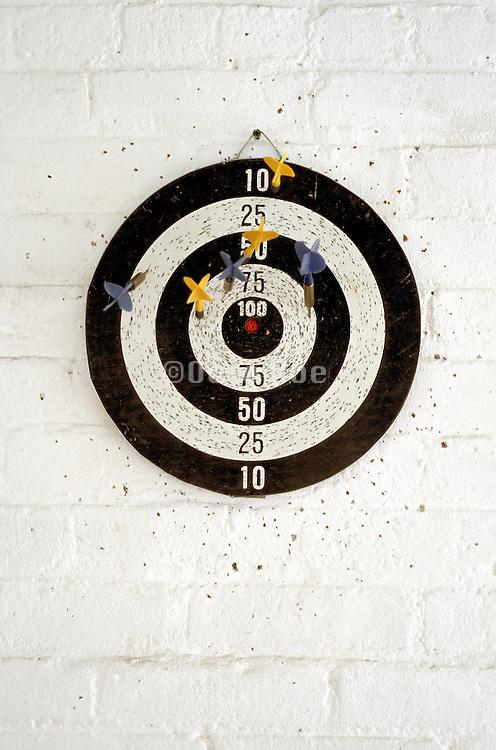 darts on dart board on white painted brick wall