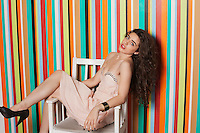 Portrait of a seductive young woman sitting on chair against colorful striped background
