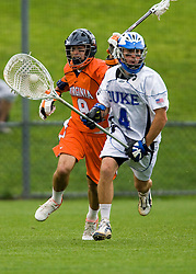 Duke Goalie Dan Loftus (4) clears the ball past Virginia attackman Danny Glading (9).  The #2 ranked Duke Blue Devils defeated the #3 ranked Virginia Cavaliers 11-9 in the finals of the Men's 2008 Atlantic Coast Conference tournament at the University of Virginia's Klockner Stadium in Charlottesville, VA on April 27, 2008.