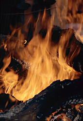 Vertical image of fire, with what appears to be a head with a gaping mouth, tow eyes and hair