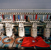 Automated stitching machine works on badges for the elite 'Red Arrows', Britain's prestigious Royal Air Force aerobatic team at Dale Techniche, Nelson, Lancashire. Every Winter, the Red Arrows place about 40 pilot suit orders and 180 blue (support ground crew) suits. Tricia adjusts her thread while the suit is complete on her work bench. The clothing factory also designs the Red Arrows badges, each requiring 15,000 stitches. All suits are made from Nomex by the Du Pont corporation, containing 5% Kevlar. Flame-retardant, they fit exactly each team member. Fouteen different measurements are taken before the first suit is cut, each one requiring approximately three metres of dyed cloth. When a suit is complete, each one is signed inside by the machinist.