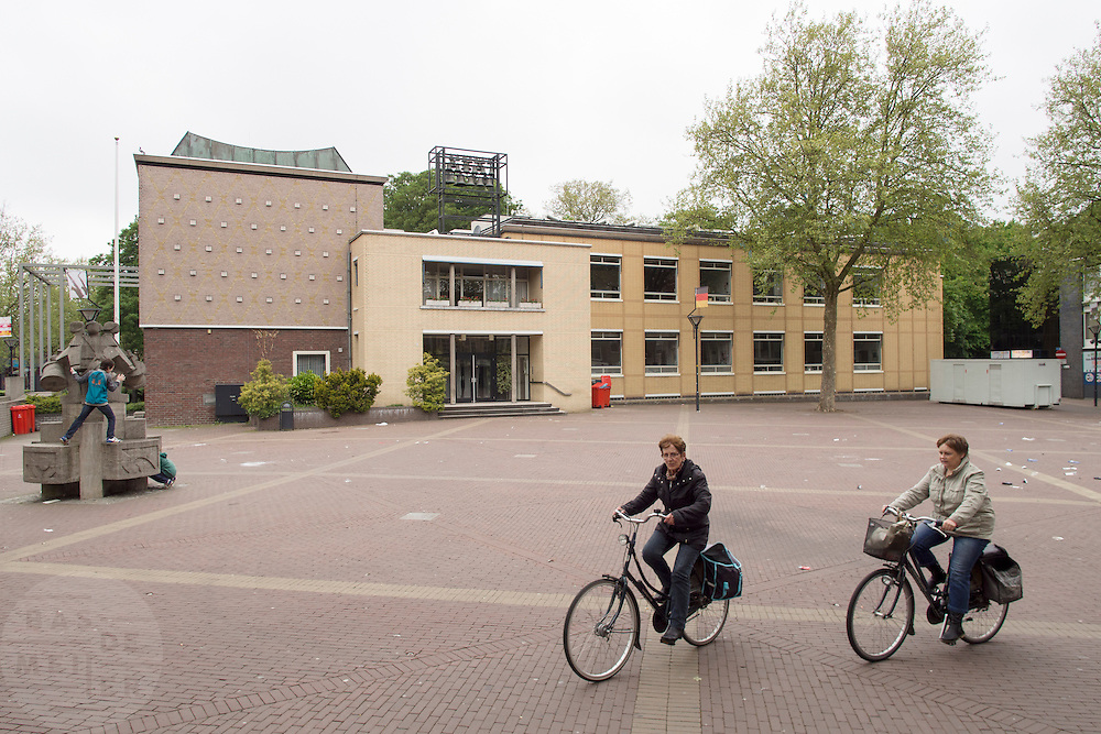 Vrouwen fietsen over het Raadhuisplein bij het stadhuis in Zevenaar, een plaats in de streek De Liemers in het oosten van Nederland.<br /> <br /> Women cycling on the Town Hall Square at the town hall in Zevenaar, a place in the region the Liemers in the east of the Netherlands.