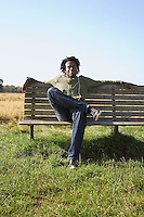 Man sitting on bench in field