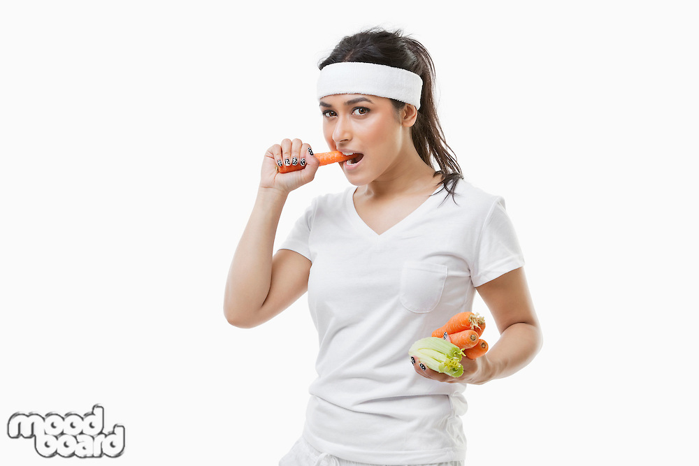 Portrait of young sportswoman eating carrot over white background