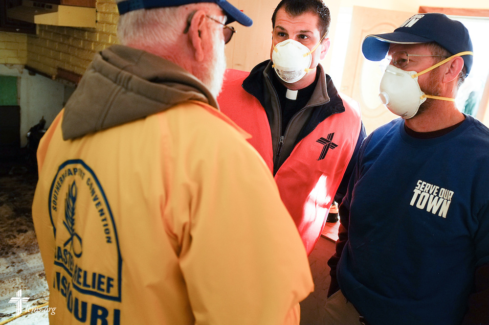 The Rev. Ross Johnson, director of LCMS Disaster Response, coordinates plans with a Missouri representative of the Southern Baptist Convention Disaster Relief, and a volunteer from the New Beginnings Lutheran Church in Pacific, Mo.,as the three join other volunteers from the International Center of The Lutheran Church–Missouri Synod during a cleaning event at a flooded home in Fenton on Thursday, Jan. 14, 2016. LCMS Communications/Erik M. Lunsford