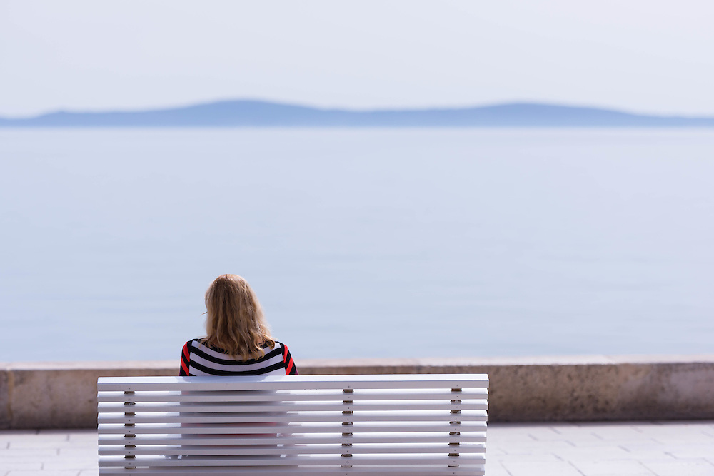 As a cool evening begins, a young woman looks out to the island of Brac from a bench on Split Riva.