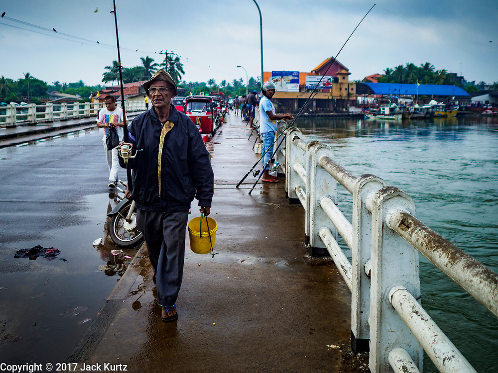 08 OCTOBER 2017 - NEGOMBO, WESTERN PROVINCE, SRI LANKA: Men fish off of a highway bridge in Negombo, north of Colombo. Fish is an important source of protein for many Sri Lankans.    PHOTO BY JACK KURTZ