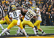 November 05, 2011: Iowa Hawkeyes running back Marcus Coker (34) pushes his way to a 4 yard touchdown run as Michigan Wolverines cornerback Troy Woolfolk (29) and Michigan Wolverines safety Jordan Kovacs (32) try to stop him during the first quarter of the NCAA football game between the Michigan Wolverines and the Iowa Hawkeyes at Kinnick Stadium in Iowa City, Iowa on Saturday, November 5, 2011. Iowa defeated Michigan 24-16.