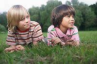 Portrait of two boys (7-9)  lying in meadow looking away