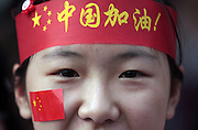 """A woman wears a headband reading """"Go China"""" and a flag sticker on her face at the Olympic Torch relay in the southern city of Wuhan, China."""