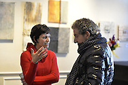 "Roslyn, New York, USA. January 31, 2015. At Artists Reception for ""The Alchemists"" is artist Karine Falleni (wearing red sweater) exhibiting work documenting movement, including installation with green automotie tape, at Bryant Library. Curated by Ellen Hallie Schiff."
