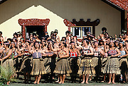 Maori women dancing at tribal gathering in front of the Wharenui meeting house at the Marae in New Zealand