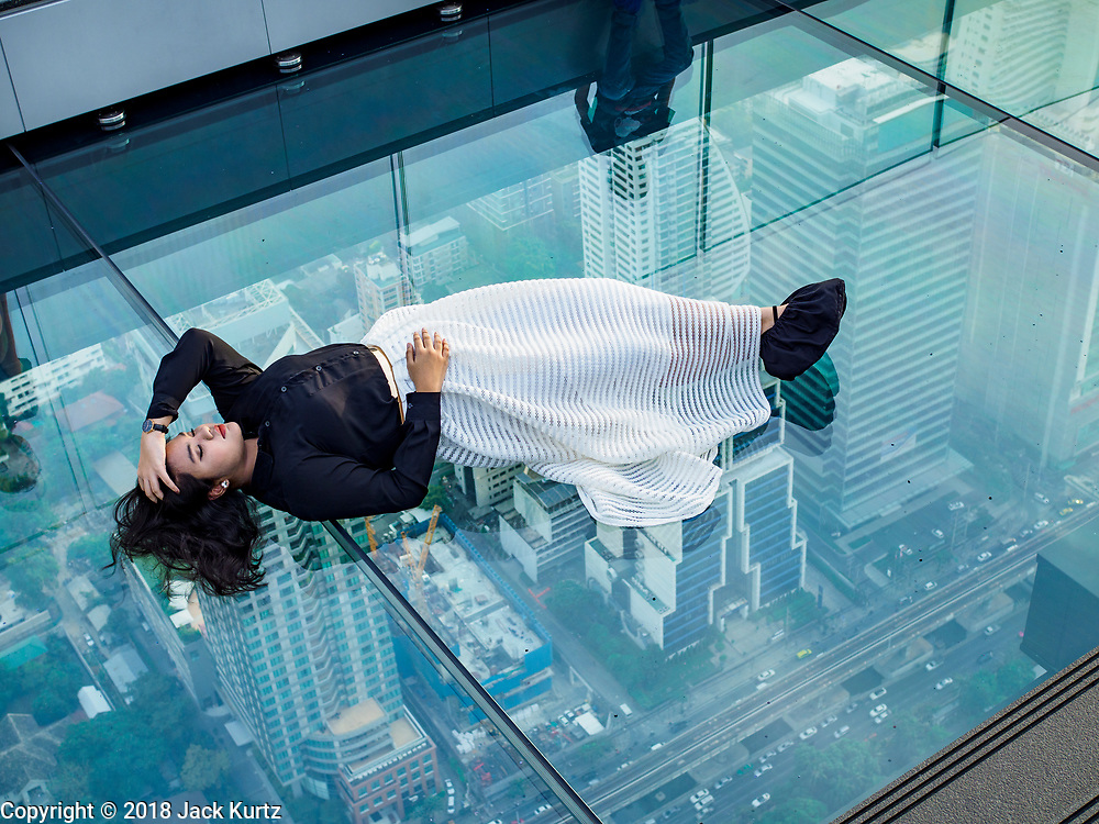 "27 DECEMBER 2018 - BANGKOK, THAILAND:  People on the ""glass tray,"" a glass overlook that sticks out over the south edge of the Maha Nakhon Tower. The MahaNakhon Skywalk, at the top of the King Power Maha Nakhon Tower, is 1,030 feet (314 meters) above street level. It is the tallest building and highest vantage point in Bangkok. The skywalk opened in November and has been drawing large crowds.    PHOTO BY JACK KURTZ"