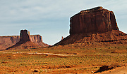 The tourist cars are dwarfed by the immense rock formations. Driving in Monument  Valley, Utah.