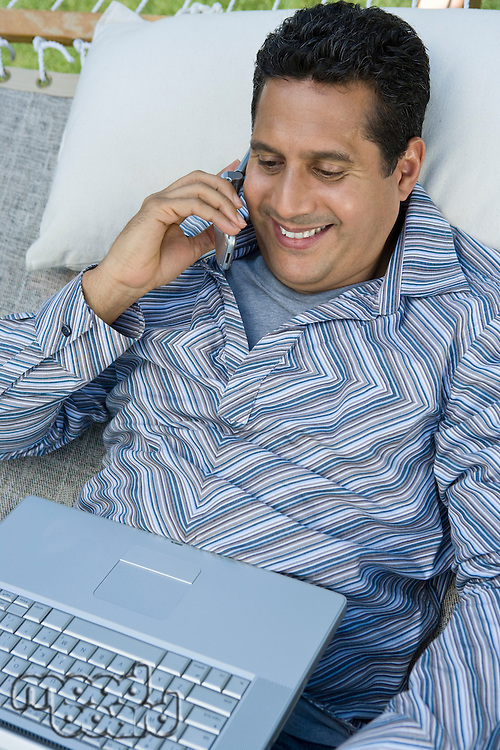 Man using mobile phone and laptop in hammock