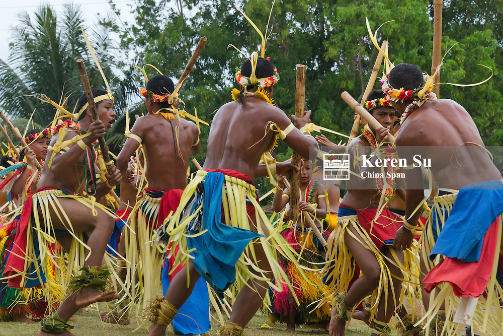 Yapese boys and girls in traditional clothing dancing with bamboo pole at Yap Day Festival, Yap Island, Federated States of Micronesia