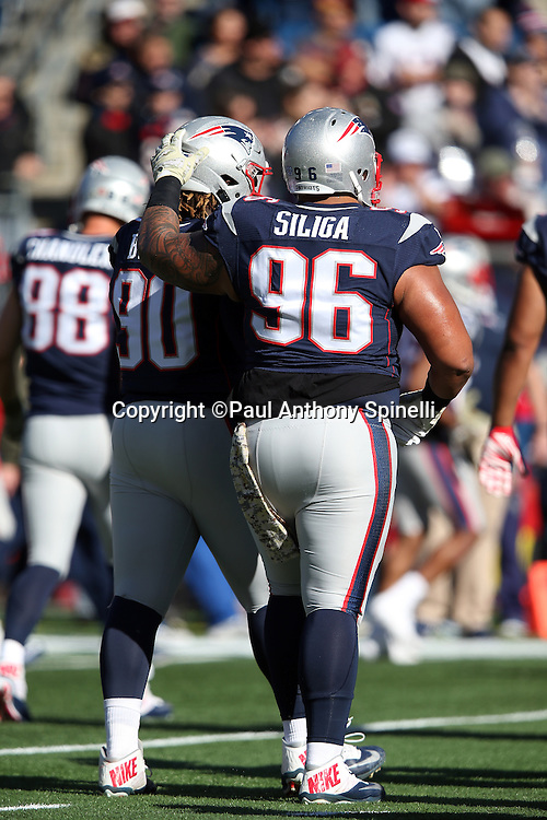 New England Patriots defensive tackle Malcom Brown (90) gets a pat on the helmet from New England Patriots defensive tackle Sealver Siliga (96) during a break in the action during the 2015 week 9 regular season NFL football game against the Washington Redskins on Sunday, Nov. 8, 2015 in Foxborough, Mass. The Patriots won the game 27-10. (©Paul Anthony Spinelli)