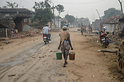 A woman carries buckets of water through a street in village Gorikothapally, Telangana, Indiia, on Friday, February 8, 2019. Photographer: Suzanne Lee for Safe Water Network