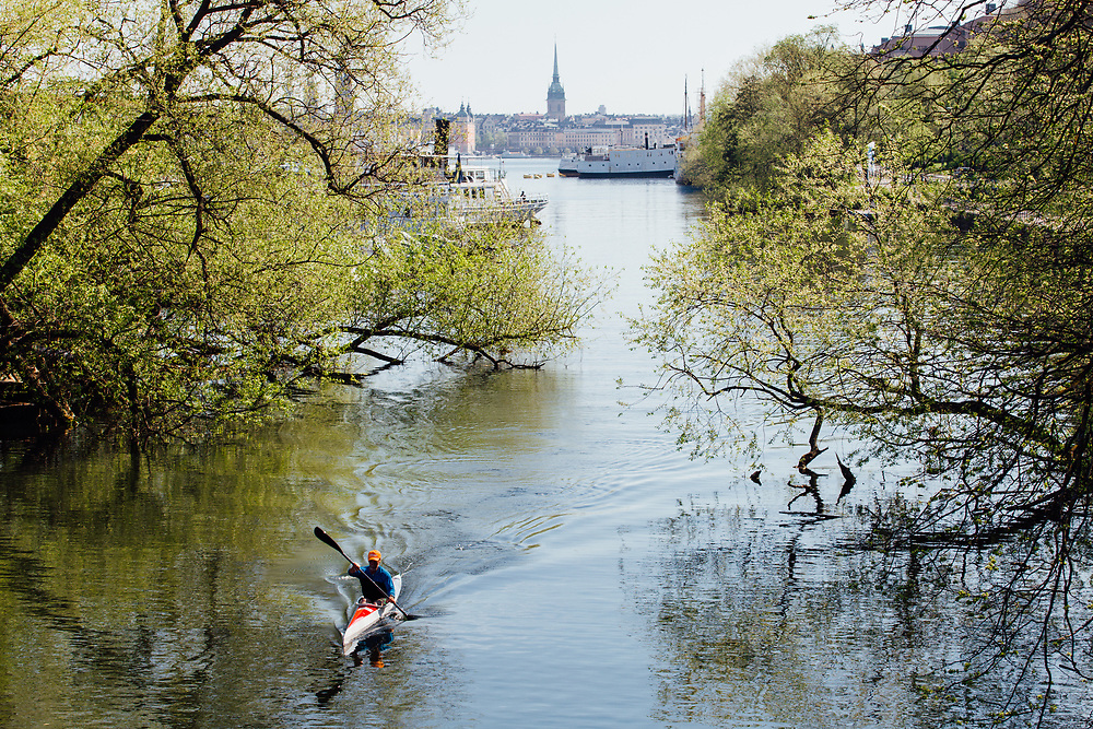 A kayaker at Lake Mälaren, Stockholm.  View taken from bridge connecting to Långholmen with Stockholm city in the background.  Riddarholmen Church is in the top center of the image.