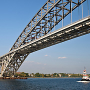 Tugboat passing under the Bayonne Bridge on the Kill Van Kull. The Bayonne Bridge, which is the third longest steel arch bridge in the world, connects Bayonne, New Jersey with Staten Island. It opened in 1931.