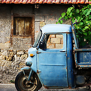 A blue Moto Guzzi Ercole beside a home in Fondi, Italy.<br />