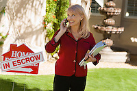 Estate agent using mobile phone at in front yard of house portrait