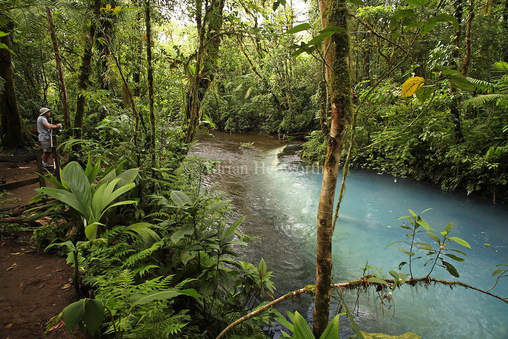 Tourist at the source of Rio Celeste (Blue River) in Tenorio Volcano National Park, Costa Rica. The blue coloration is a result of sulphurous gas from the volcano seeping up through the river bed and mixing with calcium carbonate in the water.<br />