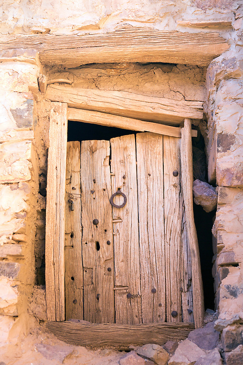 Close up of an old door to a storage chamber inside the Ighrem Granary, Souss Massa Draa, Southern Morocco, 2016-05-26.<br /><br />The Ighrem 'agadir' (singular form of granary in Tamazert Amazigh dialect) is a fortified Berber collective granary.<br /><br />The granary structures (Igoudar - plural form of granary in the Tamazert Amazigh dialect) weren't only built for storing harvests, medicines and possessions; the Amazigh ancestors also constructed them to function as an ancient form of a 'high security bank vault.'<br />The Anti Atlas and the Souss ranges are no strangers to war and conflict. The mountain terrains have been home to many an Amazigh uprising against the central governments during Arab rule and early French Occupation.<br />Although each granary is unique in design, their bee hive like labyrinth interiors of interconnecting tunnels, ladders and passageways holding padlocked chambers collectively resemble a style of architecture that Tolkien might have imagined.<br /><br />Most of the igoudar that remain are thought to date to the 16th and 17th century, although the tradition of building and using collective granaries is estimated to be as old as a millennia.<br /><br />One year of low rainfall can make life very difficult for the mainly self sufficient populous of the Anti Atlas range, who would have been ever more dependent upon the fruits of their harvest during the time of structures development.<br /><br />The crops which are agriculturally viable amid the dramatic climate conditions of the Anti Atlas, such as saffron, almonds, and argan are high in value, with saffron only offering a short annual harvesting window and the stigmas needing optimum storage conditions to preserve life span. <br /><br />Everything from important documents, money and jewellery to the seasons harvest could be stored inside the locked chambers. These well ventilated, shaded rooms built from thick stone walls remain at cool temperatures during high heats. It is possibl