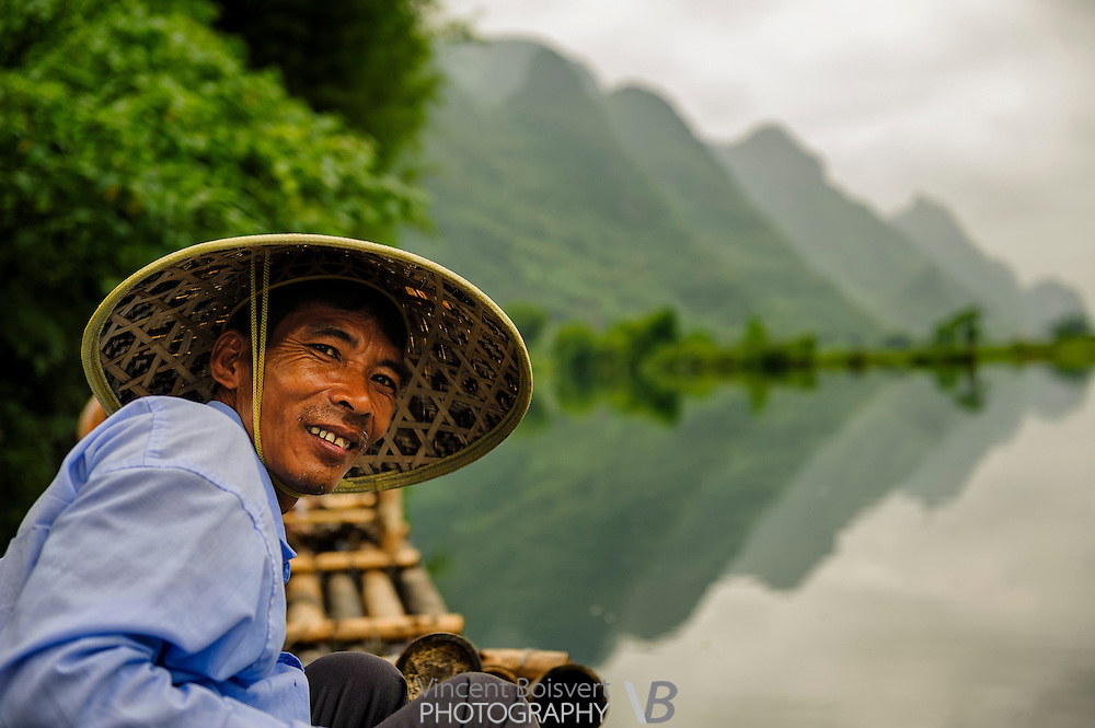 A portrait of a bamboo raft driver smilling with karst formation and yulong river in background