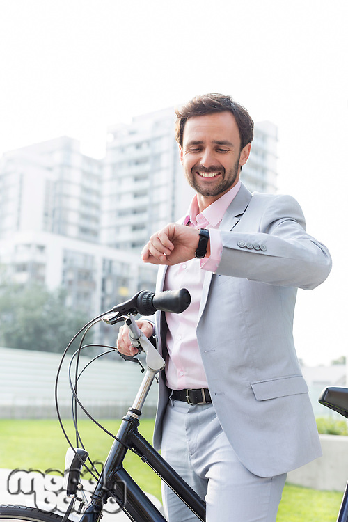 Happy businessman with bicycle checking time outdoors
